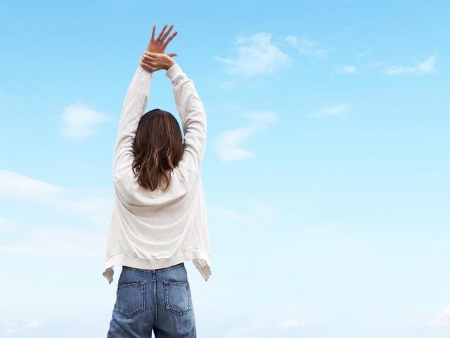 腕を真上に挙げる女性